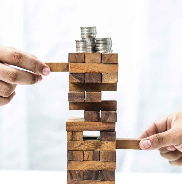 Stack of coins balancing on building block tower