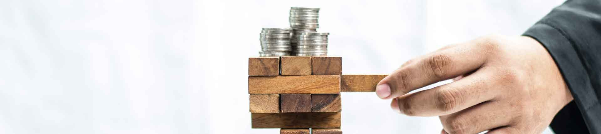 Coins balancing on a block tower