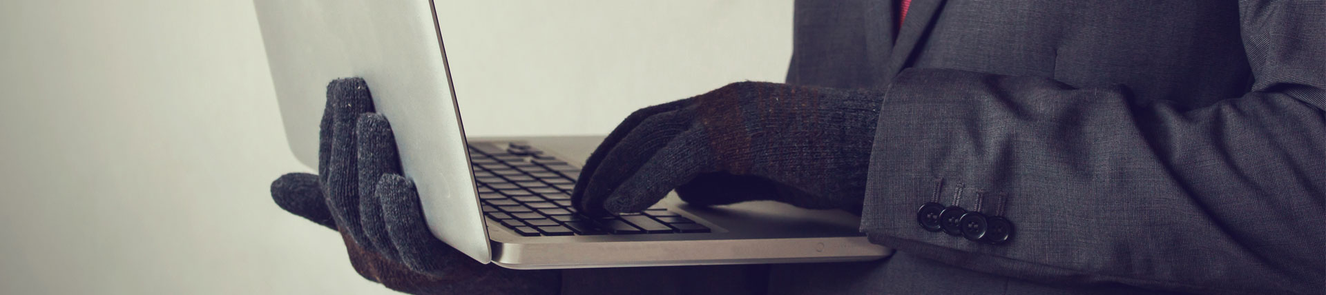 man wearing gloves on a laptop