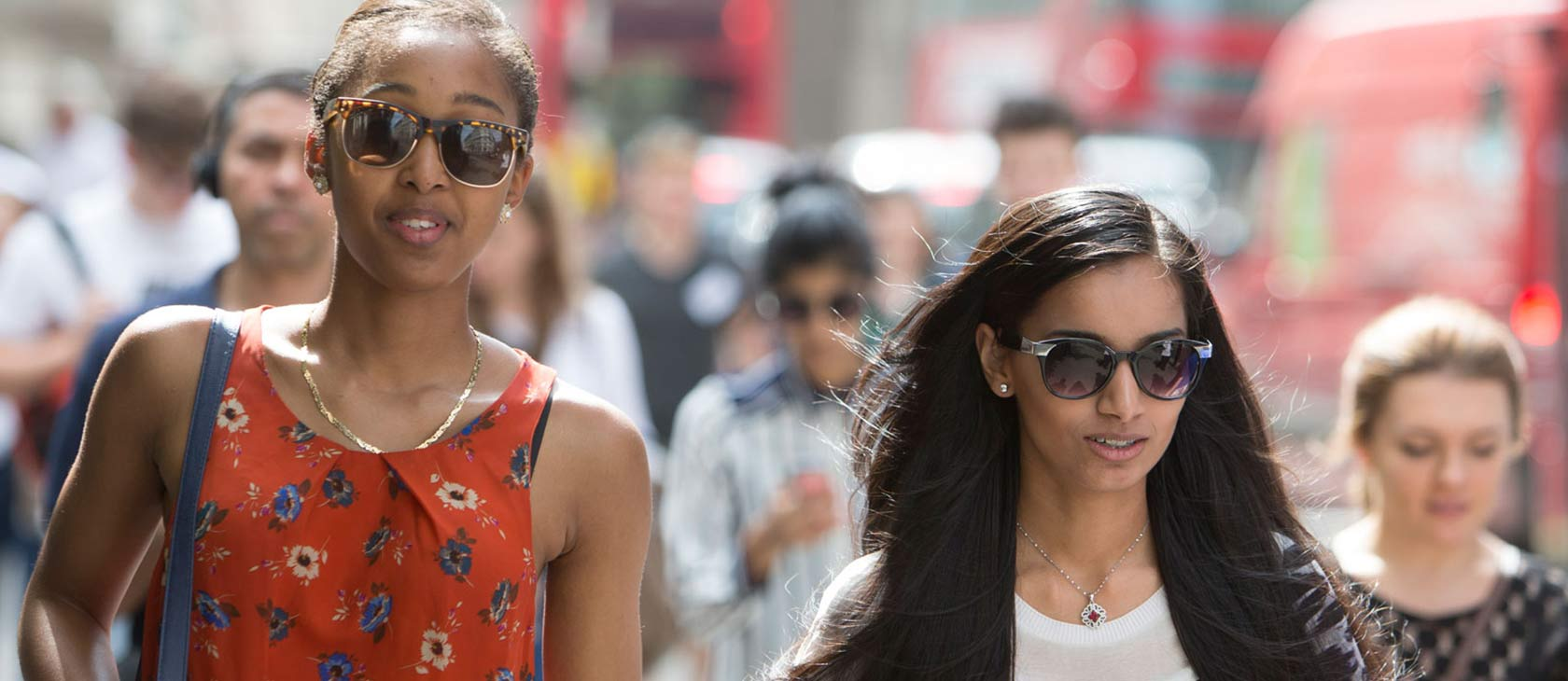 Two girls wearing summer dresses walking in London street