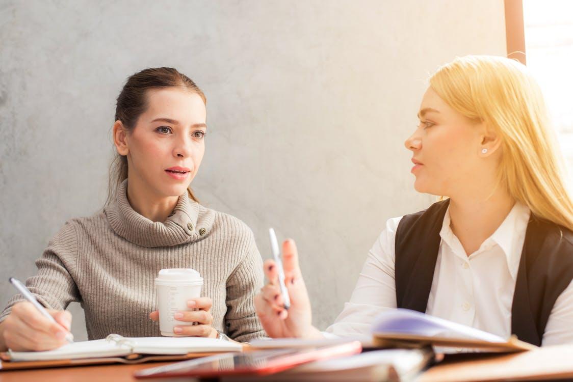 two-women-speaking-at-desk