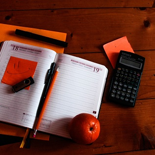 Calculator, stationery and orange