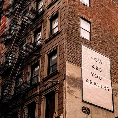 Building with fire escapes and message asking how you are