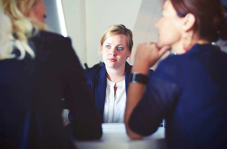 Woman in office suit speaking to others