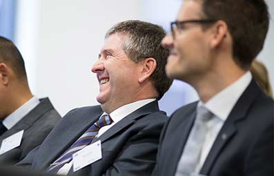Male-professionals-laughing-at-conference